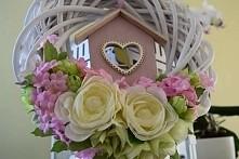 Kwiecisty wianek z różowym domkiem.