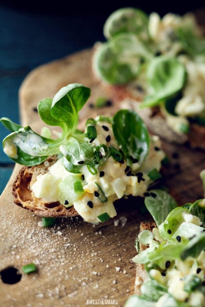 Pasta jajeczna z marynowanym ogórkiem     Składniki 4 porcje      3 jajka, ugotowane na twardo (np. według tej metody)     2 łyżki majonezu     sól i świeżo zmielony czarny pieprz     pieczywo, np. domowy razowy chleb z grubą i chrupiącą skórką     2 - 3 łyżki posiekanego szczypiorku     czarny sezam lub czarnuszka     garść roszponki lub rukola skropiona oliwą extra vergine  Ogórek w słodko-kwaśnej marynacie:      1 średni ogórek gruntowy     sok z 1 limonki     skórka z 1/2 limonki     1 łyżka octu ryżowego     1 i 1/2 łyżeczki brązowego cukru