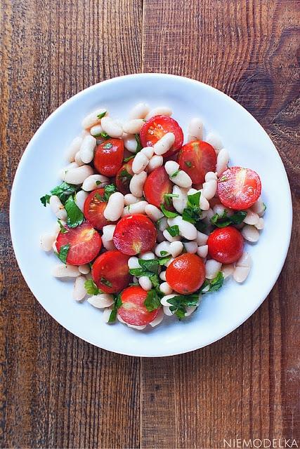 Sałatka z białą fasolą, pomidorkami koktajlowymi i natką pietruszki  Składniki: 1 puszka białej fasoli 250 g pomidorków koktajlowych posiekana natka pietruszki (ilość dowolna) 2 łyżki oliwy z oliwek 2 łyżka soku z cytryny sól, czarny pieprz  Sposób przygotowania: 1.Fasolę odsączyć z zalewy i przepłukać pod wodą. Pomidorki koktajlowe umyć, osuszyć i przeciąć na pół. 2.Wymieszać oliwę z oliwek z sokiem z cytryny i dodać sól z pieprzem. To jest nasz dressing. 3.Fasolę, pomidorki koktajlowe i posiekaną natkę pietruszki umieścić w misce. Dodać dressing, wszystko dobrze wymieszać i odstawić na 15-20 minut.