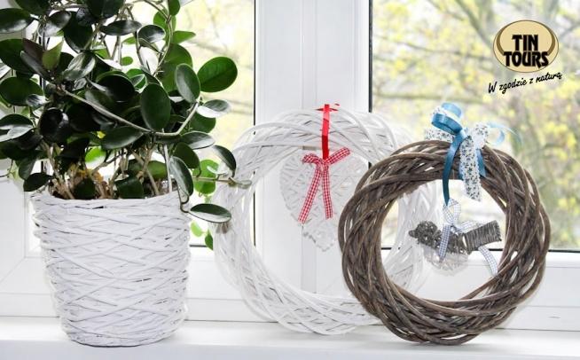 Dwa wiklinowe wianki i pasująca osłona na kwiatek tworzą ładną dekorację okna.