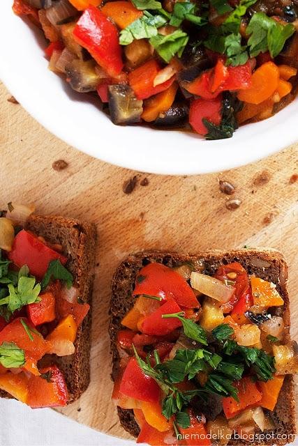 Pikantne leczo z bakłażanem Składniki: 1 duży bakłażan 1 duża czerwona papryka 1 cebula 2 średnie pomidory 2 średnie marchewki 2 łyżki oliwy 1 ząbek czosnku sól, pieprz, ostra papryka Sposób przygotowania: 1.Wszystkie warzywa umyć. Cebulę obrać, posiekać w kostkę i zeszklić na oliwie. 2.Marchewkę obrać, pokroić w pół krążkii. 3.Paprykę umyć, przekroić na pół, oczyścić z nasion oraz pokroić w kostkę. Marchewkę z papryką dodać do cebuli i przesmażyć 3-4 minuty. 4.Pomidory pokroić w kostkę i dodać do pozostałych warzyw na patelni i przesmażyć 3-4 minuty. 5.Następnie dodać bakłażana pokrojonego w kostkę. Wszystko dokładnie wymieszać, doprawić przyprawami oraz czosnkiem przeciśniętym przez praskę. 6.Dusić około 20 minut, póki warzywa nie staną się miękkie.