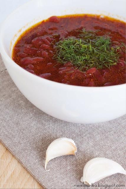 """Barszcz ukraiński Składniki: 500 g mięsa wołowego z kością 1/2 średniej kapusty głowiastej 3 średniej wielkości buraki 6 średnich ziemniaków 3 średnie marchewki 2 cebule 4 łyżki oleju 4-5 ząbków czosnku 3 liście laurowe sól, pieprz  Sposób przygotowania: 1.Mięso umyć, włożyć do dużego garnka (ja mam z Ikei - 5 l), zalać zimną wodą (do połowy garnka) i zagotować. Kiedy na wierzchu pojawią się tak zwane """"szumowiny"""", należy je dokładnie pozbierać i wyrzucić. Dodać liść laurowy i gotować przez godzinę. 2.Kapustę poszatkować i wrzucić do garnka. 3.Cebulę pokroić w drobną kosteczkę i zeszklić na rozgrzanej patelni z 2 łyżkami oleju. 4.Marchewkę obrać, zetrzeć na tarce o dużych oczkach i dodać do cebuli. Smażyć 5 minut i dodać do garnka. 5.Buraki obrać, pokroić w słomkę i smażyć 5 minut na rozgrzanej patelni z 2 łyżkami oleju. 6.Ziemniaki obrać, pokroić w kostkę i wrzucić do garnka. 7.Gotować zupę jeszcze 20-25 minut. Doprawić solą z pieprzem i dodać przeciśnięty czosnek."""