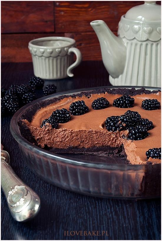 TARTA CZEKOLADOWA Z JEŻYNAMI Tarta czekoladowa z jeżynami o mocnym i intensywnym smaku dla fanów czekolady. Nie wymaga pieczenia przez co wykonasz ją szybciej i na pewno jest mniej skomplikowana. Tarta czekoladowa jest na spodzie z ciasteczek oreo. Zmiel je dokładnie w malakserze lub po prostu wrzuć do woreczka foliowego i kilkakrotnie pociągnij po nich intensywnie wałkiem. Im lepiej zmielone ciasteczka tym łatwiej będzie się kroiło i spód bardziej się ze sobą połączy. Spód z oreo możesz wykonasz nawet dzień wcześniej i trzymać schłodzony w lodówce. Masa czekoladowa jest bardzo prosta w przygotowaniu. Trzeba pamiętać, aby w lato kremówka była dobrze schłodzona (najlepiej całą noc w lodówce) w innym wypadku może zważyć się podczas miksowania i łączenia z czekoladą. Czekoladę użyłam dobrej jakościowo gorzkiej czekolady o wysokiej zawartości kakao oraz mlecznej, przez co nie dodawałam już do masy cukru. Podczas chłodzenia masa stężeje i stworzy fajny krem o aksamitnej konsystencji. SKŁADNIKI NA SPÓD Z OREO: 350 g zmielonych ciastek oreo 100 g masła, temp. pokojowa 1 łyżka kakao SKŁADNIKI NA KREM CZEKOLADOWY: 100 g mlecznej czekolady 100 g gorzkiej czekolady 450 ml śmietanki kremówki 30% DODATKOWO: ok. 100 g jeżyn Zmielone ciasteczka oreo łączymy razem z przesianym kakao oraz masłem, aż masa będzie wilgotna. Formę na tartę o średnicy około 24 cm smarujemy lekko masłem i wykładamy na dno i boki masę z ciasteczek. Dociskamy i wkładamy na godzinę do lodówki. 100 ml śmietanki podgrzewamy razem z czekoladami, aż masa będzie jednolita i składniki rozpuszczone. Pozostałą kremówkę ubijamy na sztywną masę, następnie cały czas miksując dodajemy po łyżce ostudzoną i jeszcze płynną masę z czekolady. Gotowy krem wykładamy na spód i dekorujemy jeżynami. Owijamy folią i wkładamy do lodówki na kilka godzin, a najlepiej na całą noc.