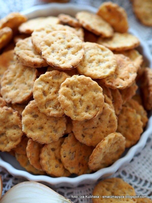 Ciasteczka cebulowe do piwa albo wina czas przygotowania: 20 minut + czas chłodzenia ciasta i pieczenia składniki: 350 g mąki pszennej + trochę do podsypywania 150 g masła 100 g kremowego twarożku naturalnego 1 jajko 1 łyżeczka proszku do pieczenia 1 łyżeczka soli 1 łyżeczka papryki słodkiej mielonej 1 łyżeczka kminku mielonego 250 g cebuli białej.Jak zrobić ciasteczka z cebulą? 2 większe cebule obrałam i pokroiłam w bardzo drobną kosteczkę. Mąkę przesiałam, dodałam zimne masło, proszek do pieczenia, sól, paprykę i kminek. Roztarłam rękami aż powstał tak jakby mokry piasek i grudki tłuszczu nie były wyczuwalne. Dodałam serek i jajko oraz cebulę, zagniotłam ciasto. Odłożyłam je do lodówki na 30 minut żeby nieco stężało. Schłodzone ciasto podzieliłam na kilka mniejszych części. Podsypując mąką rozwałkowywałam każdą na cienki placek - im cieniej tym lepiej. Foremką wycinałam małe ciasteczka i układałam je gęsto na blasze wyłożonej papierem do pieczenia. Ciasteczka piekłam ok. 12 minut w piekarniku nagrzanym do 200 st. C. Są gotowe kiedy ładnie się zezłocą. Upieczone i ostudzone przechowuję w szczelnie zamykanym pojemniku żeby nie zwilgotniały.