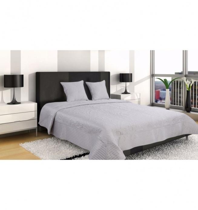 Piękna narzuta na łóżko wymiarach 160x220 cm + 2 poszewki 45x45 cm. Narzuta z efektownymi wzorami ornamentowymi. Dookoła obszyta pikowanym materiałem. Narzuta z naszyciami tworzącymi efektywne tłoczenia. Wyjątkowa ozdoba i dekoracja każdej sypialni. Materiał to matowa satyna 100 % poliester w kolorze srebra.