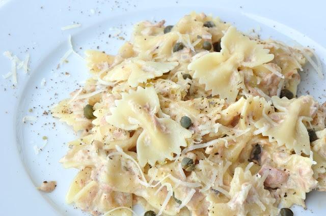 Kokardki z tuńczykiem w sosie śmietankowym  Składniki: 2 - 3 porcje:      200 g makaronu - kokardki     puszka tuńczyka w oliwie     2 łyżki kaparów     1/2 cebuli     suszone oregano     4 łyżki oliwy extra virgin     1/2 szklanki płynnej śmietanki do sosów 30% (lub serka mascarpone)     sól, świeżo zmielony czarny pieprz,      tarty parmezan     świeże oregano lub bazylia do dekoracji    Sposób przygotowania: Makaron gotuję al dente w osolonej wodzie i mieszam z 3 łyżkami oliwy. Na patelni na pozostałej oliwie podduszam pokrojoną cebulę, ale nie zrumieniam, dodaję kapary, tuńczyka z oliwą, chwilę podgrzewam. Na sam koniec dodaję śmietankę oraz ugotowany makaron. Doprawiam solą, czarnym pieprzem i oregano, posypuję tartym parmezanem.