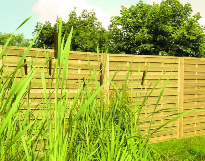 Dywan z trawy na tarasie i barierka w formie zielonego płotu. Efekt: niesamowita świeżość na tarasie.