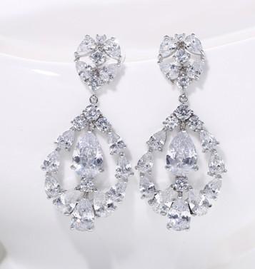 Piękne kolczyki ślubne Opis : Materiał : stop jubilerski platerowany białym złotem (GP) rodowany (RP) Kolor : srebrny Rodzaj kamieni : wysokiej jakości sztuczny Szwajcarski diament ( bardzo zbliżony do prawdziwego) klasy AAA+ . Twardość w skali Mohsa 8-9 ( kryształki Swarovskiego : 6-7, prawdziwe diamenty 10) Sposób mocowania kamieni : ręczne w zaczepach  Kolczyki nie czarnieją, ani nie uczulają- idealne dla alergików Nie zawierają niklu, litu, ani ołowiu  WYSOKA JAKOŚĆ- GWARANCJĄ ZADOWOLENIA :)  Wymiary : największa szerokość: 2,5cm długość : 5cm  Rodzaj zapięcia: sztyft sprzedam cena: 140zł