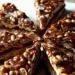CARAMEL BROWNIE TOWER  (z Coffee Heaven :))  Składniki:  Masa czekoladowa Brownie: • 200 g gorzkiej czekolady 70% • 200 g masła • 3 jajka • 220 g drobnego cukru lub cukru pudru (można dać mniej) • 120 g mąki  Masa karmelowa z mascarpone i orzeszkami ziemnymi: • 1/3 kostki masła • 1/2 szklanki cukru • 2 szklanki mleka w proszku • 100 g solonych orzeszków ziemnych • 250 g sera mascarpone  Polewa karmelowa: • 1/3 kostki masła • 1/3 szklanki cukru • 1/2 szklanki śmietanki kremówki 30% • opcjonalnie - 4 pełne łyżki Glukozy (np. Delecty)  oraz na wierzch: • 100 g solonych orzeszków ziemnych  Przygotowanie: Orzeszki ziemne (200 g) wysypać na blaszkę do pieczenia i wstawić do piekarnika nagrzanego do 160 stopni. Zrumienić na jasno brązowy kolor (około 10 minut). Ostudzić. Zamiast w piekarniku, orzechy można też lekko zrumienić na patelni. Małą blaszkę o wymiarach 20 x 24 cm lub jeszcze mniejszą, wysmarować tłuszczem i wyłożyć papierem do pieczenia. ( U mnie proporcje na tortownicę o średnicy 22cm)  Masa czekoladowa Brownie: piekarnik nagrzać do 170 stopni. Roztopić czekoladę w rondelku razem z masłem, uważając aby nie podgrzać za bardzo masy, ostudzić. Jajka ubić na puszystą pianę razem z cukrem (około 10 minut), następnie wymieszać z ostudzoną masą czekoladową. Na koniec delikatnie połączyć z przesianą mąką. Masę wylać do przygotowanej blaszki i piec przez 25 minut.  Masa karmelowa z mascarpone i orzeszkami ziemnymi: masło roztopić w rondelku z grubym dnem, wsypać cukier. Podgrzewać na małym ogniu, cały czas mieszając drewnianą łyżką (około 15 minut). Uważać, aby nie przypalić masy. Gdy cukier zbrązowieje wlać 1/2 szklanki wody. Gotować przez chwilkę, aż zbrylony karmel ponownie będzie gładką, brązową masą. Trochę przestudzić i do jeszcze ciepłego wsypać mleko w proszku, zmiksować na gładką masę. Połowę (100 g) uprażonych orzeszków ziemnych drobno posiekać lub grubo zmielić w młynku do kawy. Dodać do ostudzonej masy karmelowej i wymieszać z serem mascarpone.  Polewa karmel