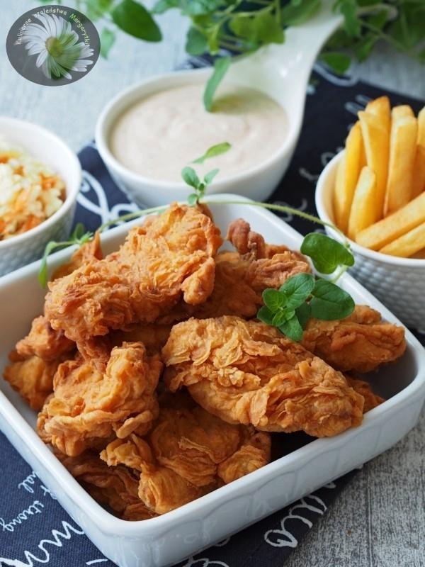 Pikantne Stripsy a'la KFC Nie ukrywam, lubie Fast-Food'y, zwłaszcza kurczaka i ZWŁASZCZA tego z KFC. Dlatego dziś mam dla was fajny przepis znaleziony na blogu margarytki. Smacznego :) Składniki na 12 kawałków: 2 duże filety z kurczaka (moje ważyły 450 g) ½ łyżeczki soli ½ łyżeczki świeżo mielonego pieprzu ½ łyżeczki mielonego chili 1 łyżeczka słodkiej mielonej papryki Ciasto: 1 duże jajko albo 2 małe (moje ważyło 80 g) 1/3 szklanki mleka (u mnie 2 %) ¾ szklanki mąki pszennej – użyłam wrocławskiej typ 500 ½ łyżeczki soli ½ łyżeczki mielonego pieprzu ¾ łyżeczki mielonego chili 1 łyżeczka słodkiej mielonej papryki ½ łyżeczki mielonego imbiru Dodatkowo: 1 szklanka mąki pszennej (u mnie wrocławska typ 500) + 2 łyżki skrobi kukurydzianej albo ziemniaczanej około 1- 1,5 l oleju do smażenia (ja użyłam niedużego rondla, więc wlałam 700 ml oleju rzepakowego) Filety z kurczaka opłukać, osuszyć papierowym ręcznikiem, pokroić na dowolnej wielkości kawałki – ja każdy filet pokroiłam na 6 części. Włożyć do miski, wsypać sól, pieprz, chili i słodką czerwoną paprykę. Dokładnie wymieszać, aby każdy kawałek mięsa był pokryty przyprawami. Przykryć miskę folią spożywczą i wstawić do lodówki na kilka godzin (może spokojnie stać całą noc). Jajko, mleko, mąkę i przyprawy wsypać do miski (ja użyłam pojemnika od blendera) i wszystko razem dobrze zmiksować. Ciasto powinno być dosyć gęste. Wlać je do miski z kawałkami kurczaka i wymieszać. Każdy kawałek mięsa musi być obtoczony w cieście. Do miski albo plastikowego pojemnika wsypać mąkę pszenną i skrobię kukurydzianą albo ziemniaczaną, dokładnie wymieszać. Wkładać po 3 – 4 kawałki kurczaka i potrząsać miską (pojemnikiem) tak, aby każdy kawałek kurczaka był dobrze obtoczony mąką. W rondlu rozgrzać olej, musi być go na tyle dużo, aby kawałki kurczaka swobodnie w nim pływały. Temperatura oleju musi być dosyć wysoka (około 175 stopni) aby panierka nie nasiąknęła tłuszczem, ale też zbyt gorący olej może spowodować, że panierka się szybko zrumieni,