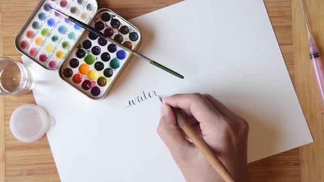 Filmik ang. pokazujący w jaki sposób za pomocą farb akwarelowych można pisać kolorowe litery