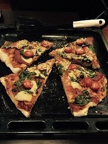 pizza domowej roboty z salami, szpinakiem i pomidorkami cherry
