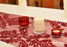 Bordowy bieżnik z ornamentami, szklane świeczniki - dostępne w wypożyczalni.