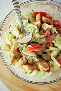 Sałatka z kurczakiem i słodkim jogurtowym sosem  kapusta pekińska (około 1 i 1/2 kubka posiekanej kapusty) 1/2 średniego, zielonego ogórka 2 małe pomidory 2 łyżki posiekanej drobno cebuli kilka zielonych oliwek 1/2 jabłka 2 rzodkiewki 100 ml kremowego jogurtu naturalnego 2 łyżeczki soku z cytryny szczypiorek 1 łyżeczka miodu ---------- 130 g piersi z kurczaka 1 łyżeczka miodu 1 łyżeczka ostrej musztardy 1/2 łyżeczki ostrej papryki  Dzień przed przygotowaniem sałatki kroimy piersi z kurczaka w sporą kostkę i w miseczce zalewamy marynatą z miodu, musztardy i ostrej papryki, przechowujemy przez noc w lodówce.  Kapustę siekamy i opłukujemy na sitku, dodajemy na nie również umyte i pokrojone pomidory, aby trochę obciekły.  Ogórka i rzodkiewkę kroimy wzdłuż a następnie na cienkie plasterki (połówki). Oliwki przekrawamy w pół, a cebulę bardzo drobno siekamy. Wszystkie warzywa wkładamy do sporej miski i dodajemy również pokrojone w sporą kostkę jabłko.  W kubeczku łączymy jogurt z łyżeczką miodu, sokiem z cytryny oraz sporą ilością posiekanego szczypiorku, mieszamy dokładnie i zalewamy sałatkę.  Na patelni podsmażamy kawałki kurczaka i dodajemy do reszty składników - całość dokładnie łączymy z sosem.