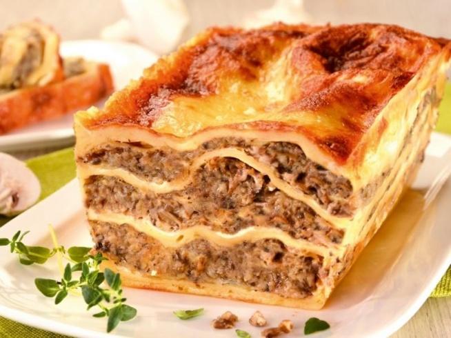 Lasagne z pieczarkami i serem żółtym       12 płatów makaronu lasagne     400 g pieczarek     cebula     oliwa     300 g startego sera żółtego     zioła prowansalskie     sól     pieprz     śmietana 18%     bułka tarta       Płaty makaronu lasagne namocz w wodzie, aby odrobinę zmiękły. W tym czasie przygotuj farsz.     Cebulę obierz, pokrój w kostkę i podsmaż na złoto.     Pieczarki pokrój na ćwiartki, podsmaż razem z cebulką. Dopraw na patelni solą, pieprzem oraz ziołami prowansalskimi.      Gdy przestygną, drobno posiekaj.     Pieczarki wymieszaj z taką ilością bułki tartej, żeby masa była dość zwarta.     Naczynie żaroodporne wysmaruj masłem. Na dnie połóż pierwszą warstwę płatów makaronu.     Posmaruj cienko śmietaną i oprósz serem. Na ser wyłóż 1/3 masy pieczarkowej. Przykryj kolejnym blatem.      Powtarzaj aż do wyczerpania składników.     Wierzch dodatkowo obsyp startym serem.     Lasagne z pieczarkami wstaw do piekarnika nagrzanego do 180 stopni C i piecz około 30 minut.