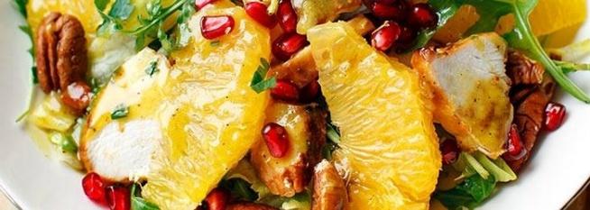 Sałatka z kurczakiem, pomarańczą i orzechami Soczysta sałatka idealna na sezon jesienno-zimowy. Grillowana pierś kurczaka, pomarańcza, granat i orzechy pekan. Z pysznym miodowym winegretem z sokiem z pomarańczy. Dodatek szczypty cynamonu czyni całość jeszcze bardziej interesującą w smaku :-) Składniki 2 porcje, po 509 kcal 1 filet z kurczaka (ok. 200 g) 1/3 opakowania rukoli (ok. 30 g) 1/4 główki sałaty lodowej 1 pomarańcza 1/3 owocu granatu 60 g orzechów pekan (lub włoskich) Sos 3 łyżki miodu 2 łyżki musztardy miodowej 1 łyżka oliwy extra vergine 1 łyżka soku z cytryny 2 łyżki soku z pomarańczy 1/3 łyżeczki mielonego cynamonu Przygotowanie Składniki sosu wymieszać w kubeczku, doprawić solą i pieprzem. Filet z kurczaka pokroić na 4 mniejsze kawałki, doprawić solą, wysmarować oliwą i położyć na rozgrzanej patelni grillowej. Grillować po 4 minuty z dwóch stron. Kawałki kurczaka posmarować łyżką sosu i dalej grillować przez ok. 1,5 minuty na nieco mniejszym ogniu, przewrócić na drugą stronę, posmarować kolejną łyżką sosu i grillować jeszcze przez ok. 1 minutę po czym zdjąć z patelni i odłożyć. Pozostały sos wykorzystać do sałatki. Rukolę opłukać na sitku, odcedzić, osuszyć, wymieszać z posiekaną sałatą lodową i wyłożyć na 2 talerze. Pomarańcze obrać i wyfiletować (ostrym nożem wykroić cząstki miąższu pomiędzy błonkami), z reszty pomarańczy wycisnąć sok i zachować go do sosu. Owoc granatu pokroić na ćwiartki i wyłuskać ziarenka. Orzechy lekko zrumienić na patelni, grubo posiekać. Sałatę i rukolę doprawić solą i pieprzem, dodać pokrojonego kurczaka, cząstki pomarańczy, posypać granatem i orzechami włoskimi. Polać pozostałym sosem.