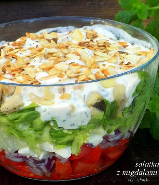 Sałatka z fetą i migdałami  Składniki: 3-4 pomidory 1 czerwona cebula 150 g sera feta 1/2 główki kapusty lodowej 1 podwójna pierś z kurczaka 150 ml jogurtu naturalnego 2 łyżki majonezu ząbek czosnku kilka gałązek koperku 2 łyżki płatków migdałowych sól, pieprz 2 łyżki oleju  Kurczaka pokroić w kostkę, lekko posolić, doprawić pieprzem i usmażyć. Jogurt wymieszać z majonezem, solą, pieprzem, przeciśniętym przez praskę czosnkiem i posiekanym koperkiem. Fetę delikatnie pokroić w kostkę. Sałatę lodową pokroić, cebulę posiekać. Z pomidorów usunąć gniazda nasienne a miąższ pokroić. Migdały uprażyć na suchej patelni. W misce układać warstwami: najpierw pomidory, następnie cebulę, fetę, sałatę, kurczaka. Na wierzch wylać sos czosnkowy i posypać całość migdałami.