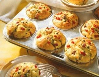 Składniki  300 g mąki 200 g wędzonej szynki 2 pęczki szczypiorku 80 g masła 2 jajka 1/8 l mleka 1/8 l maślanki 4 łyżeczki proszku do pieczenia 1 łyżeczka marynowanych ziaren zielonego pieprzu masło do foremek  Etapy przygotowania  1  Szynkę drobno pokroić. Szczypiorek opłukać, osuszyć i drobno posiekać. Roztopić masło. 2  Wymieszać mąkę z proszkiem do pieczenia. Jaja ubić z mlekiem i masłem, dodać do mąki i wymieszać. Wymieszać szynkę ze szczypiorkiem i pieprzem. Foremki wysmarować masłem i wyłożyć do nich ciasto. Piec w piekarniku rozgrzanym do 180 stopni (elektryczny), 160 stopni (z termoobiegiem), pozycja 2-3 (gazowy) przez 25-30 minut. 3  Wskazówka: do masy można dodać 100 g startego sera, jak ementaler lub gouda, aby smak był bardziej wyrazisty.