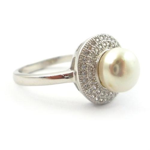 Pierścionek srebrny z perłą i cyrkoniami - Srebrny Pies  Pierścionek wykonany ze srebra próby 925 z naturalnej perły hodowlanej.  Pierścionek z naturalną perłą hodowlaną otoczoną drobnymi cyrkoniami i srebrem. Pierścionek charakteryzuje ponadczasowy szyk, który nigdy nie wyjdzie z mody.
