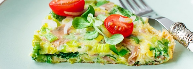 OMLET Z DUSZONYMI PORAMI SKŁADNIKI 2 PORCJE, PO 422 KCAL 4 jajka 2 łyżki mleka 1 por 3 plasterki wędliny (użyłam włoskiej mortadeli) garść szpinaku po 1 łyżce oliwy i masła 50 g sera brie do dekoracji: pomidorki koktajlowe, roszponka PRZYGOTOWANIE Odciąć zielone liście pora. Białą i jasnozieloną część przekroić wzdłuż na 2 połówki, opłukać, osuszyć i pokroić na plasterki. Na patelnię wlać łyżkę oliwy i włożyć pory, doprawić solą, smażyć mieszając przez ok. minutę, następnie przykryć pokrywką i dusić ok. 2 minuty na małym ogniu. Zdjąć pokrywę i smażyć mieszając jeszcze przez 1-2 minuty. Na koniec dodać opłukany szpinak i wymieszać. Do miski wbić jajka, dodać mleko, doprawić solą i pieprzem i roztrzepać widelcem. Dodać zeszklone pory ze szpinakiem, pokrojony na kawałeczki ser brie, pokrojoną w kosteczkę wędlinę i wymieszać. W międzyczasie nagrzewać piekarnik (np. górną grzałkę grillową lub tylko górną grzałkę). Rozgrzać większą patelnię o średnicy ok. 24 cm, włożyć masło i rozprowadzić po całej patelni. Wlać masę jajeczną i wyrównać powierzchnię. Smażyć na umiarkowanym ogniu przez ok. 2 - 3 minuty aż od spodu omlet się zetnie i lekko zrumieni. Wówczas wstawić patelnię do piekarnika na ok. 3 minuty (rączkę można pozostawić na zewnątrz i nie zamykać do końca piekarnika) lub aż omlet będzie ścięty (nie będzie to trwało zbyt dużo, nawet przy pieczeniu z uchylonym piekarnikiem).