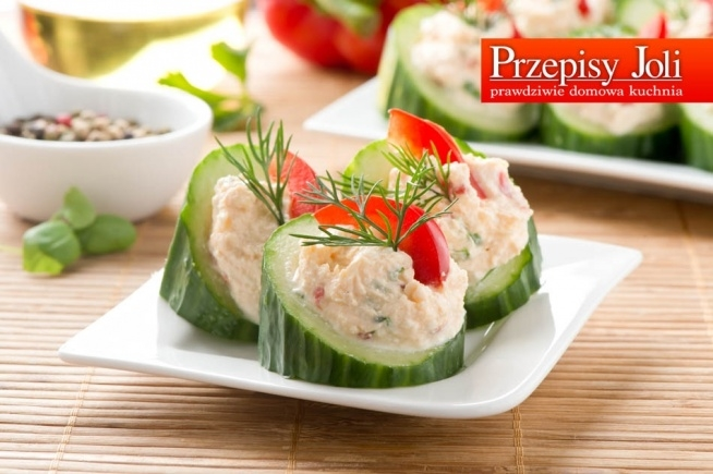 Ogórki faszerowane. Składniki: 2 długie zielone ogórki 200 g tłustego sera feta 1 łyżka majonezu 0,5 czerwonej papryki 1-2 ząbki czosnku 0,5 pęczka szczypiorku sól, pieprz czarny kilka gałązek świeżego koperku i kawałek czerwonej papryki do dekoracji  Wykonanie: Paprykę umyć, wysuszyć i pokroić w drobna kostkę. Szczypiorek umyć, wysuszyć i drobno posiekać. Ser feta dokładnie rozetrzeć łyżką z majonezem, dodać przeciśnięty przez praskę czosnek, pokrojoną paprykę i posiekany szczypior, całość dokładnie wymieszać. Dodać sól i pieprz czarny, i jeszcze raz wymieszać. Ogórki dokładnie umyć i pokroić na około 4 cm kawałki (plastry). Następnie każdy kawałek przeciąć na pół pod ukosem, tak aby otrzymać dwie części, z jednej strony proste a z drugiej ukośne. Z każdego kawałka ogórka, łyżką do melonów lub małą łyżeczką, wydrążyć trochę miąższu (od ukośnej strony, prosta strona stanowi podstawę). Tak przygotowane ogórki faszerować nadzieniem z sera feta. Przed podaniem udekorować gałązkami koperku i paseczkiem czerwonej papryki.