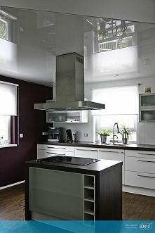 Biały, połyskujący sufit oraz kontrastowa wyspa na środku kuchni - funkcjonal...
