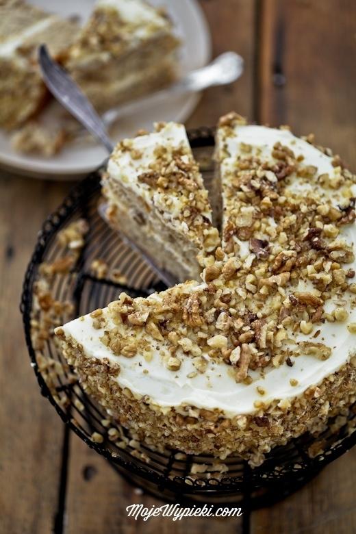 CIASTO KOLIBER  Składniki na ciasto:  200 ml oleju rzepakowego 3/4 szklanki drobnego cukru do wypieków 3 jajka, białka i żółtka oddzielnie 3 łyżki mleka 100 g świeżego ananasa  2 bardzo dojrzałe banany 300 g mąki pszennej 1 łyżka proszku do pieczenia 1 łyżeczka cynamonu 75 g orzechów pekan, posiekanych* Wszystkie składniki powinny być w temperaturze pokojowej. Mąkę przesiać z proszkiem do pieczenia, odłożyć.  Do naczynia przelać olej. Dodać cukier, mleko i żółtka, wymieszać rózgą kuchenną.   W malakserze (lub blenderem) zmiksować ananasa i banany na puree. Puree dodać do mieszanki z olejem i wymieszać widelcem lub rózgą kuchenną. Dodać przesianą mąkę z proszkiem, wymieszać szpatułką. Na sam koniec wmieszać cynamon i orzechy,  W osobnym naczyniu ubić białka, na sztywną pianę. Pianę dodać do wcześniej przygotowanego ciasta i delikatnie wymieszać szpatułką.  Dwie foremki o średnicy 20 cm wysmarować masłem, wyłożyć papierem do pieczenia, samo dno. Ciasto podzielić na dwie równe części, następnie przelać do foremek.  Piec w temperaturze 170ºC przez około 30 - 40 minut lub do tzw. suchego patyczka. Wyjąć, wystudzić.  Krem:  150 g masła 120 g cukru pudru 450 g serka kremowego typu philadelphia 1 łyżeczka ekstraktu z wanilii Wszystkie składniki powinny być w temperaturze pokojowej.  W misie miksera utrzeć masło z cukrem pudrem do otrzymania jasnej i puszystej masy maślanej. Stopniowo dodawać serek kremowy, cały czas miksując. Dodać ekstrakt z wanilii i zmiksować.   Ponadto:  dwie garści posiekanych orzechów pekan* Wykonanie  Na paterze ułożyć pierwszy blat ciasta. Na niego wyłożyć 1/4 kremu i wyrównać. Przykryć drugim blatem ciasta. Wierzch i boki ciasta równo przykryć pozostałym kremem. Ozdobić posiekanymi orzechami.  Przechowywać w lodówce. Wyjać z niej minimum 30 minut przed podaniem.  * Oryginalnie do ciasta dodawane są orzechy pekan - są one stosunkowo miękkie i maślane w smaku. Można je zastąpić orzechami włoskimi.  Smacznego :-).