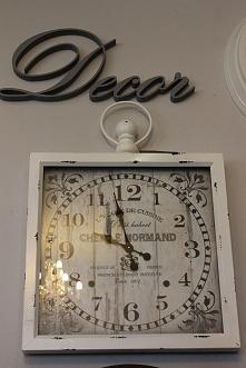 Zegar w metalowej obudowie w kolorze białym o wymiarach 60x60x6cm.