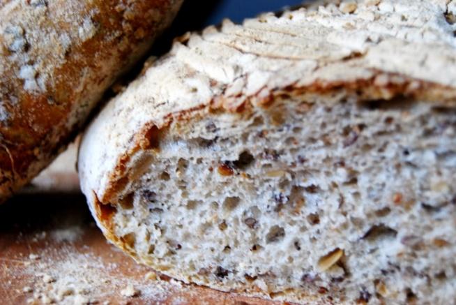 Chleb z ziarnami na zakwasie Zaczyn: 2 łyżki zakwasu żytniego; 85 g letniej wody; 70 g mąki pszennej (u mnie typ 650). Namaczanka: 40 g ziaren siemienia lnianego; 110 g ciepłej, przegotowanej wody. Ciasto właściwe: Cały zaczyn; Cała namaczanka; 350 g mąki pszennej (u mnie typ 650); 35 g mąki żytniej razowej (typ 2000); 160 g wody; 55 g ziaren słonecznika; 25 g ziaren sezamu; 10 g soli. przygotowania: Na rozgrzaną, suchą (tj. bez dodatku tłuszczu) patelnię wsypać ziarna słonecznika i sezamu i uprażyć na złoty kolor. Wystudzić. W misce (u mnie od robota kuchennego) wymieszać ze sobą (łyżką lub mikserem przy pomocy haka do ciasta drożdżowego) składniki zaczynu tj. mąkę pszenną, letnią wodę i zakwas. Tak przygotowany zaczyn przykryć czystą ściereczką, owinąć szczelnie folią (ja wkładam do foliowej reklamówki i szczelnie ją zawiązuję) i odstawić w ciepłe miejsce na 12 godzin (u mnie cała noc). Podobnie do miseczki wsypać ziarna siemienia lnianego, zalać ciepłą wodą, przykryć czystą ściereczką i odstawić w ciepłe miejsce na 12 godzin (u mnie cała noc). Po upływie tego czasu do miski z zaczynem dodać pozostałe składniki ciasta właściwego tj. obie mąki, wodę, namaczankę, sól,  uprażone ziarna i dobrze wyrobić (ja wyrabiam mikserem przy pomocy haka do ciasta drożdżowego). Wyrobione ciasto przykryć czystą ściereczką, owinąć szczelnie folią (ja wkładam do foliowej reklamówki i szczelnie ją zawiązuję) i odstawić w ciepłe miejsce na 2 godziny do wyrośnięcia, odgazowując/składając je w tym czasie 1 raz (po upływie 60 minut) - filmik obrazujący składanie ciasta chlebowego - autor: weekendbakery.com. Następnie uformować bochenek (filmik obrazujący formowanie okrągłego bochenka - autor: danusia555), włożyć go delikatnie, zlepieniem do góry, do dobrze obsypanego koszyka do wyrastania chleba, przykryć czystą ściereczką, owinąć szczelnie folią (ja wkładam do foliowej reklamówki i szczelnie ją zawiązuję) i odstawić do wyrośnięcia w ciepłe miejsce na 3 godziny. Po tym czasie chleb przeło