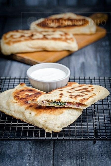 TURECKI CHLEBEK :D Ciasto: - 300 g mąki pszennej - 90 ml ciepłej wody - szczypta soli - 10 g świeżych drożdży - 1 łyżka oliwy Farsz: - 100 g sera feta - 100 g liści szpinaku - 5 listków mięty - 1 czerwona cebula - 2 ząbki czosnku - pieprz WYKONANIE Drożdże rozpuszczamy z łyżką mąki w kilku łyżkach ciepłej wody. Odstawiamy w ciepłe miejsce i czekamy, aż zaczną pracować. Następnie dosypujemy pozostałą mąkę, sól, dolewamy wodę i zagniatamy elastyczne ciasto. Miskę natłuszczamy oliwą i przekładamy do niej ciasto, pozostawiamy na około godzinę do wyrośnięcia. W międzyczasie przygotowujemy farsz. Oczyszczone liście szpinaku gotujemy przez chwilę w odrobinie wody. Na osobnej patelni podsmażamy pokrojoną w plasterki cebulę i czosnek. Dodajemy do podgotowanego szpinaku, doprawiamy pieprzem i listkami mięty (jest to bardzo istotny składnik, nadaje daniu niesamowity smak). Wyrośnięte ciasto zagniatamy ponownie i dzielimy na sześć porcji. Każdą z nich rozwałkowujemy na prostokąt o wymiarach ok. 12 cm x 18 cm, na połowę każdego prostokąta nakładamy szpinak i posypujemy rozdrobnioną fetą. Składamy ciasto w pół i zlepiamy brzegi. Patelnię lekko naoliwiamy i smażymy każdy chlebek po około 2 minuty z każdej strony. Podajemy z sosem jogurtowym. Smacznego  Przepis: kulinarne.info
