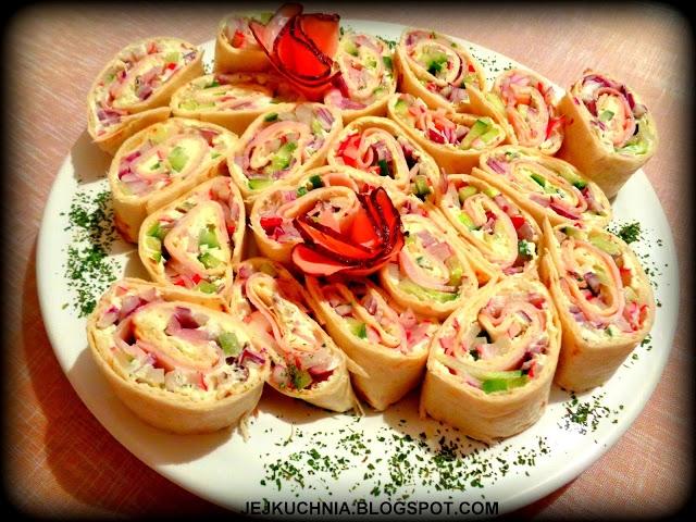 KOLOROWE ROLADKI Z WARZYWAMI        3 placki tortilli,     opakowanie serka Almette o ulubionym smaku,     9 plasterków szynki,     większa cebula czerwona,     1/2 większego ogórka,     8 rzodkiewek.       Wszystkie warzywa siekam w drobne paseczki lub kosteczkę.     Każdy placek tortilli smaruję serkiem, wykładam posiekane warzywa, następnie po 3 plastry szynki (obok siebie).     Całość ściśle zwijam w roladkę, kroję na grubsze plastry.