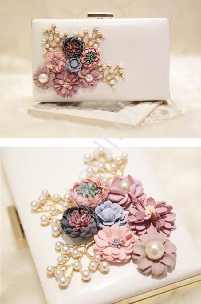 Modna biała torebka z kwiatami 3D  Biała torebka z kwiatami wykonanymi z pianki i perełkami. Torebka w formie kopertówki. Idealna na ślub czy na wieczór. Okucie i łańcuszek w kolorze złotym. Torebka wykonana z białej ekoskórki.