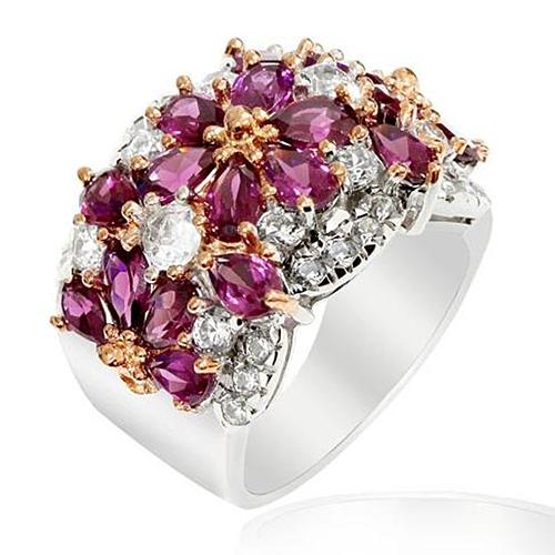 """FRIDA Srebrny pierścionek, obrączka z rodolitami  Elegancki i wyrazisty pierścionek - obrączka. Srebro rodowane i rodolity. Kamienie, ułożone jak płatki kwiatów a pomiędzy nimi drobne """"kwiatuszki"""" z różowego złota. Całość niezwykle wytworna. Ilość i szlif kamieni nadają blask, tak że pierścionek promienieje wewnętrzną energią.  Elegancki dodatek do popołudniowego stroju lub jako uzupełnienie wieczorowej kreacji. Będzie wybornie pasować do kreacji w ecru, pastelowych różach, szarości i czerni.  Pierścionek ten, to doskonały pomysł na prezent, z okazji ważnej rocznicy Waszego związku lub by wyrazić żywione uczucia, szczególnie dla osoby, ceniącej sobie zdecydowaną biżuterię z klasą."""