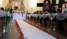 Dekoracja kościoła świecami, mieczykami z akcentem czerwonej róży.