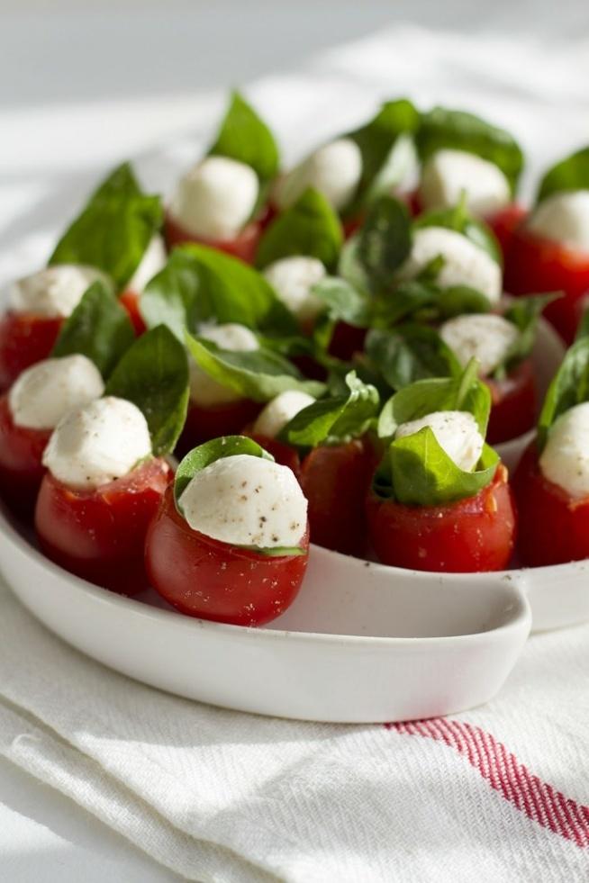 odciąć czubek i wyjąć wnętrze pomidorków koktajlowych. do każdego włożyć listek lub dwa bazylii i połowę małej kuleczki mozzarelli. całość skropić oliwą i oprószyć pieprzem.