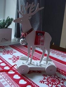 Renifer-zabawka na kółkach z dzwoneczkiem i kieszonkami na grzbiecie.W kieszo...