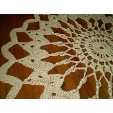 Piękny dywan ręcznie robiony ze sznura bawełnianego w kolorze żółtym. Ma średnicę około 150 cm. Wzór ażurowy.