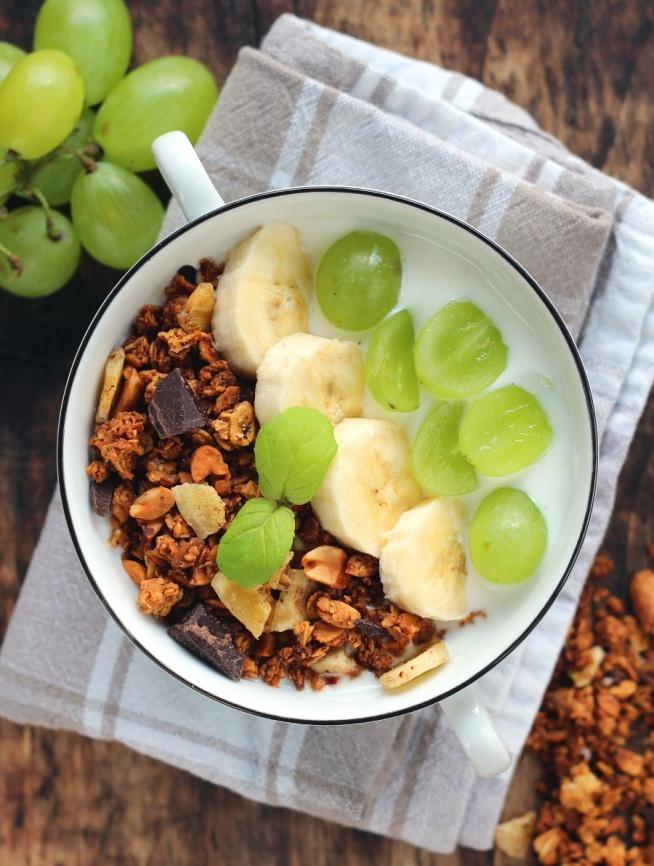 Granola bananowo-kokosowa z czekoladą  Składniki  płatki owsiane górskie, 100 g otręby owsiane, 100 g orzechy ziemne, 50 g wiórki kokosowe, 70 g cukier brązowy, 50 g banan, 1 szt. świeżo wyciśnięty sok z pomarańczy, 100 ml olej kokosowy, 1 łyżka suszone banany, 50 g gorzka czekolada, 30 g  Sposób przygotowania  Płatki, otręby, orzechy, wiórki i cukier wymieszać. Orzechy można wcześniej grubo pisiekać. Banana rozgnieść i połączyć z sokiem i roztopionym olejem. Suche składniki wymieszać z mokrymi. Przełożyć na blaszkę wyłożoną papierem do pieczenia. Równomiernie rozłożyć. Piekarnik ustawić na funkcję góra- dół i rozgrzać do 180 stopni. Piec przez 30 minut. Co 10 minut mieszać, aby granola równo się wysuszyła. Wyłączyć piekarnik, zamieszać musli i zostawić uchylone drzwiczki. Po 5 minutach przesypać granolę do pojemnika. Kiedy wystygnie dodać posiekane banany i czekoladę, zamieszać.