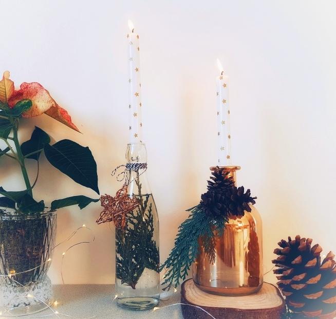 Butelkowe świeczniki ozdobione zielenią i szyszkami