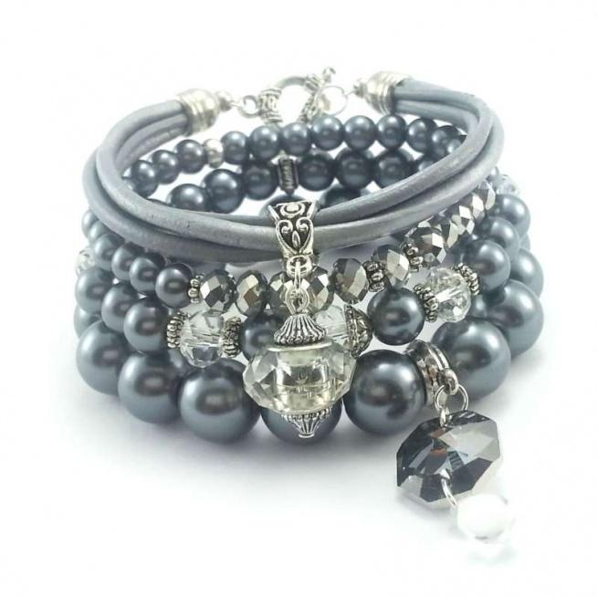ZESTAW BRANSOLETEK 4W1 SREBRNA PERŁA I SKÓRA Komplet czterech bransoletek wykonanych ręcznie. Można je nosić razem lub osobno.  Trzy bransoletki na gumce z kul perły szklanej o wielkości 12, 8, 6 mm z kryształkami szklanymi w kolorze srebrnym 6x4 mm, przeźroczystych 8x6 i przywieszki w kształcie ośmiokątu ( również kryształ szklany) o wielkości 15x15 mm. Jedna bransoletka z rzemienia ze skóry naturalnej w kolorze szarym i metalicznym srebrnym o grubości 2,5 mm z przywieszką ze szklanego, modułowego kryształka o wielkości 14 mm z zapięciem bali. Bransoletki będą pasowały na nadgarstek 15,16 cm średnicy.