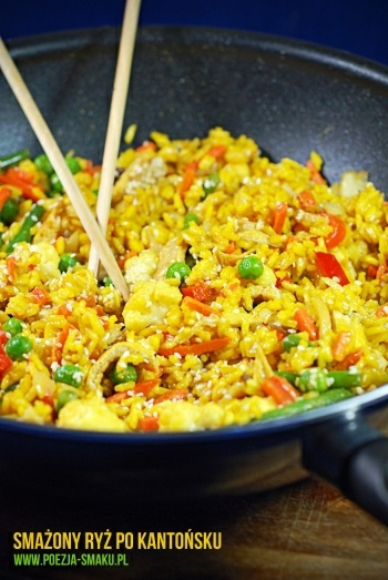 Składniki:  2 torebki ryżu (200g)1 łyżeczka kurkumy3 jajka2-3 cebulki dymki (białe i zielone części)6 łyżek sosu sojowego2 łyżki oleju sezamowego2 ząbki czosnku1/2 łyżeczki mielonego imbiru1/2 łyżeczki chili w proszkuszczypta cukru (najlepiej brązowego ale niekoniecznie)sezam do posypania (opcjonalnie)olej lub oliwa do smażeniadodatki do wyboru (warzywne, rybne lub mięsne):gotowe mieszanki warzyw mrożone, pierś z kurczaka, boczek, mielone mięso wieprzowe, łosoś, krewetki, brokuły, kalafior, por, kiełki, pędy bambusa, papryka, marchewka, fasolka szparagowa, mrożony groszek, rzodkiewka i inne.  Ryż gotujemy w osolonym wrzątku wraz z łyżeczką kurkumy przez 1-2 minuty krócej niż podano na opakowaniu. W czasie gdy ryż się gotuje, roztrzepujemy jajka i dodajemy do nich 2 łyżki sosu sojowego. Na patelni rozgrzewamy 1-2 łyżki oleju i gdy będzie gorący wlewamy jajka. Smażymy omlet – czekamy aż zetną się prawie całe i przekręcamy omlet na drugą stronę. Smażymy jeszcze chwilkę i zdejmujemy. Na woku lub bardzo dużej patelni ponownie rozgrzewamy mocno olej. Gdy będzie skwierczał dodajemy pokrojoną w kostkę cebulę, a za chwilę mięso (jeśli używamy). Solimy. Podsmażamy przez chwilę i dodajemy najtwardsze warzywa (np.: marchewka, kalafior). Ja tym razem użyłam samych warzyw. Cały czas mieszając, dodając stopniowo miększe warzywa i pokrojoną dymkę. Jeśli używamy warzyw mrożonych, nie musimy ich rozmrażać pod warunkiem, że dodajemy je partiami (musi się smażyć, a nie gotować). Omlet kroimy w paski i dodajemy do warzyw. Ugotowany ryż odcedzamy i wsypujemy na wok. Polewamy całość sosem stworzonym z 4 łyżek sosu sojowego, 2 łyżek oleju sezamowego, chili, imbiru, cukru i wyciśniętych czosnków. Mieszamy całość. Smażony ryż posypujemy sezamem i od razu podajemy.