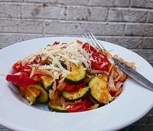 Na talerzu makaron ryżowy z warzywkami i parmezanem.