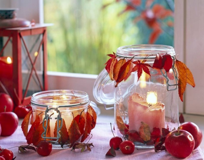 Suche liście w jednym kolorze (np. rudoczerwonym) nawlecz na nitkę i zawiąż ją w formie wianka na rancie słoika. Resztą liści wyłóż dno naczynia i wstaw do środka świeczkę.