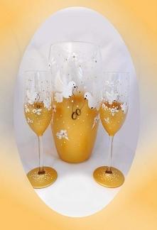 Niepowtarzalny szklany zestaw, zawierający dwa kieliszki do szampana i wazon. Na złotym tle, (które mieni się pod wpływem światła) zostały wymalowane białe kwiaty i gołębie trzy...