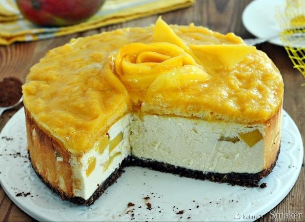 Sernik z mango       spód: 170 g ciastek     2 łyżki kakao     50 g masła     sernik: 75 dkg sera twarogowego półtłustego     250 ml śmietany kremówki 30 %     250 ml jogurtu greckiego     4 jajka     1 budyń     2/3 szklanki cukru pudru     1 cytryna     1 mango     galaretka: 1 mango duże     1 łyżeczka czubata żelatyny     2 łyżki jogurtu greckiego     1/3 opakowania galaretki cytrynowej  Spód: Ciastka rozdrabniam blenderem, przekładam do miski, dodaje kakao, roztopione masło i łączę. Formę o średnicy 22 cm jej dno wykładam papierem do pieczenia. Wykładam masę ciasteczkową, ugniatam palcami. Wstawiam do nagrzanego piekarnika temp 160 stopni góra dół na 5 minut.  Sernik: Ser miele dwa razy, przekładam do miski, dodaję jajka, cukier, budyń,jogurt, śmietanę, skórkę startą z cytryny, i sok z cytryny. Mieszam mikserem do połączenia składników, ale nie długo bo masa się napowietrzy. Mango obieram i kroje w kostkę. Na podpieczony zimny spód wylewam 1/3 masy serowej, układam połowę kostek mango, na to kolejne 1/3 masy i mango i resztę masy wylewam. Piekarnik nagrzewam do 180 stopni termoobieg, wstawiam miskę z gorącą wodą, wstawiam sernik i piekę 15 minut. Potem zmniejszam na 130 minut i piekę jeszcze 45 minut. Wyłączam piekarnik, uchylam drzwiczki i studzę sernik w piekarniku.  Galaretka:  Mango obieram, kilka plasterków owocu odcinam do róży, resztę miksuję blenderem. Żelatynę rozpuszczam w niewielkiej ilości wody, dodaję do musu mango. Połowę odlewam i dodaję jogurt. Na wystudzony sernik wylewam masę mango z jogurtem, na to mus mango. Dekoruję plastrami mango. Galaretkę rozpuszczam w 1/2 szklance wody gorącej i zacznie tężeć polewam nią róże. Sernik wstawiam do lodówki.