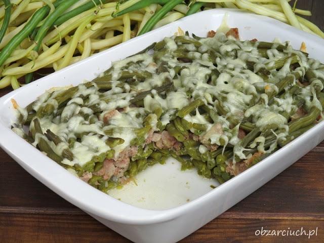 Fasolka szparagowa zapiekana z kiełbasą 1 kg zielonej fasolki szparagowej 150 g sera tartego mozzarella 100 g tartego sera żółtego Edam około 700 g kiełbasy swojskiej sól Fasolkę myjemy, obieramy i gotujemy do miękkości w lekko osolonej wodzie. Ugotowaną odsączamy. Kiełbasę kroimy w kostkę. Na dno naczynia żaroodpornego wykładamy połowę fasolki szparagowej i posypujemy ją połową sera mozzarella. Następnie układamy kiełbasę i wykładamy resztę fasolki szparagowej. Wierzch przykrywamy pozostałą mozzarellą i startym serem żółtym. Tak przygotowaną fasolkę wstawiamy do piekarnika nagrzanego do 200 st. i pieczemy około 15 min.