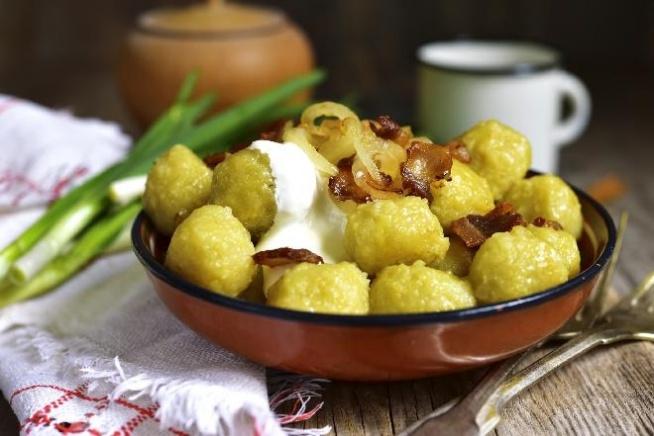 Pyzy z Różyca - przepis tradycyjnej kuchni warszawskiej 1200 g ziemniaków w skórkach - odmiana mączysta 2 cebule 200 g wędzonego boczku 40 ml oleju Boczek pokroić w cienkie paseczki i podsmażyć. Cebulę pokroić w półksiężyce i podsmażyć na oliwie. 200 g ziemniaków ugotować, pozostałe umyć i obrać, po czym zetrzeć na tarce o drobnych oczkach, przełożyć na sito i mocno odcisnąć. Musi powstać dość sucha masa. Ugotowane ziemniaki obrać i przecisnąć przez praskę. Odważyć 90 g i połączyć z 340 g odciśniętych, surowych ziemniaków. Wymieszać dokładnie i dodać skrobię, która powstała na dnie miski z płynem po odciśnięciu startych ziemniaków. Ciasto wymieszać i uformować kuleczki o średnicy około 3 cm. Pyzy ugotować w lekko osolonej wodzie na delikatnym ogniu, aż wypłyną, a następnie jeszcze 3 minuty. Ugotowane nałożyć do słoiczków lub misek i omaścić podsmażoną cebulką z boczkiem.