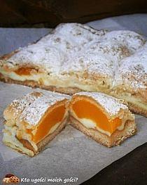Brzoskwiniotka – kruche ciasto z brzoskwiniami i budyniem    (forma ok 23×33 cm) Ciasto kruche: 2,5 szklanki mąki 250 g masła 200 g waniliowego serka homogenizowanego 2/3 szklanki cukru pudru 3 łyżki cukru z prawdziwą wanilią 1 łyżeczka proszku do pieczenia Dodatkowo: 2 budynie śmietankowe/waniliowe 3 szkl mleka  Z podanych składników zagnieść kruche ciasto (za mnie robi to robot kuchenny ;). Gdyby za bardzo się kleiło dodać jeszcze trochę mąki - ma być plastyczne. Ciasto podzielić na pół, jedną część rozpłaszczyć i schować do lodówki, drugą podsypać mąką, rozwałkować i przełożyć do blaszki wyłożonej papierem do pieczenia (ja lekko rozwałkowałam a potem porozciągałam rękami żeby wypełnić dokładnie blaszkę). Uwaga: teraz sa dwie opcje, ja z reguły stosuję tą pierwszą bo wtedy mam pewność, że nie będzie zakalca ;) a) ciasto nakłuć widelcem, włożyc do piekarnika nagrzanego do 200*C na ok 10-12 minut i upiec spód na złoto, a następnie całkowicie go wystudzić b) na surowy spód wykładamy resztę i pieczemy w całości - wtedy czas pieczenia należy wydłużyć 2. 2,5 szkl mleka zagotować z cukrem, proszek budyniowy wymieszać z zimnym mlekiem, wlać na gotujące się mleko i gotować aż zgęstnieje. Jeszcze gorący wylać na spód ciasta. 3. Brzoskwinie obrać, przekroić na pół, ułożyć na budyniu (dziurką po pestce do dołu). 4. Drugą część ciasta wyjąć z lodówki, podsypać mąką i rozwałkować, wyłożyć na brzoskwinie wciskając je lekko między owoce. Wstawić do piekarnika nagrzanego do 190*C i piec aż wierzch się zrumieni (ok 40 min, a jeśli spód nie był wcześniej podpieczony to ok 60 min).  Po wystudzeniu wstawić do lodówki. Gotowe ciasto posypać cukrem pudrem. Ja oczywiście nie wytrzymałam i zjadłam kawałek jeszcze ciepłego z gałką lodów waniliowych