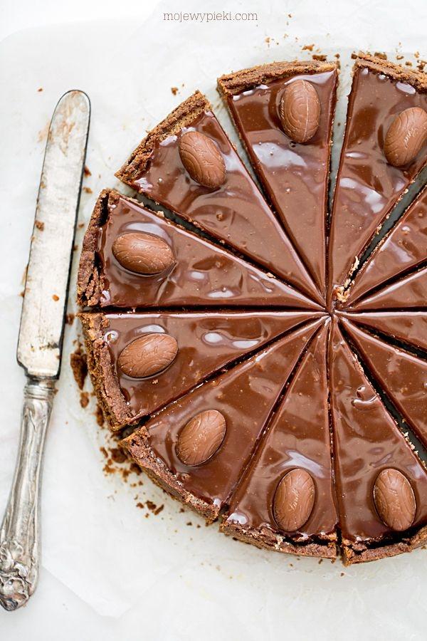 Sernik z mleczną czekoladą i jajeczkami czekoladowymi  Składniki na spód:      250 g ciastek zbożowych, pełnoziarnistych lub owsianych     80 g masła, roztopionego  Ciastka i masło wrzucić do malaksera i zmiksować do otrzymania masy ciasteczkowej o konsystencji mokrego piasku.  Tortownicę o średnicy 23 cm wyłożyć papierem do pieczenia, samo dno. Na papier wysypać ciasteczka. Wyrównać, dokładnie wklepać w dno formy i jej boki do 1/2 ich wysokości (sernik jest niski). Schłodzić w lodówce przez czas przygotowania masy serowej.  Składniki na masę serową:      350 g twarogu tłustego lub półtłustego, zmielonego przynajmniej dwukrotnie     150 ml śmietany kremówki 36%     3 duże jajka     1/3 szklanki drobnego cukru do wypieków     1 łyżeczka pasty z wanilii     1 łyżka mąki pszennej     120 g mlecznej czekolady, posiekanej lub mlecznych chocolate chips  Wszystkie składniki powinny być w temperaturze pokojowej.  Czekoladę roztopić w kąpieli wodnej lub mikrofali, przestudzić, ale powinna pozostać płynna.  W misie miksera umieścić wszystkie składniki na masę serową. Zmiksować do połączenia lub wymieszać rózgą kuchenną; nie miksować zbyt długo, by niepotrzebnie nie napowietrzać masy serowej - napowietrzony sernik mocno urośnie, a potem opadnie. Nie chcemy tego; sernik po upieczeniu powinien być równy jak stół.  Masę serową przelać na ciasteczkowy spód i piec w kąpieli wodnej* w temperaturze 160ºC przez około 50 minut. Cała powierzchnia sernika powinna być wypieczona i ścięta przy dotyku patyczkiem. W razie konieczności lekko wydłużyć czas pieczenia. Wyjąć z piekarnika, wystudzić.  Polewa z mlecznej czekolady:      100 g mlecznej czekolady     40 ml śmietany kremówki 30% lub 36%  Mleczną czekoladę (posiekaną) i kremówkę umieścić w kąpieli wodnej i roztopić nad parą, wymieszać. Lekko przestudzoną polewę rozprowadzić po serniku.  Dowolnie udekorować przed zastygnięciem polewy - u mnie to jajeczka czekoladowe.  * Sernik pieczemy w kąpieli wodnej: kąpiel wodna polega na tym, że fo