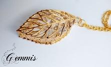 Liść w kolorze złota, a w nim uwięzione przeźroczyste kryształki. Całość zawi...
